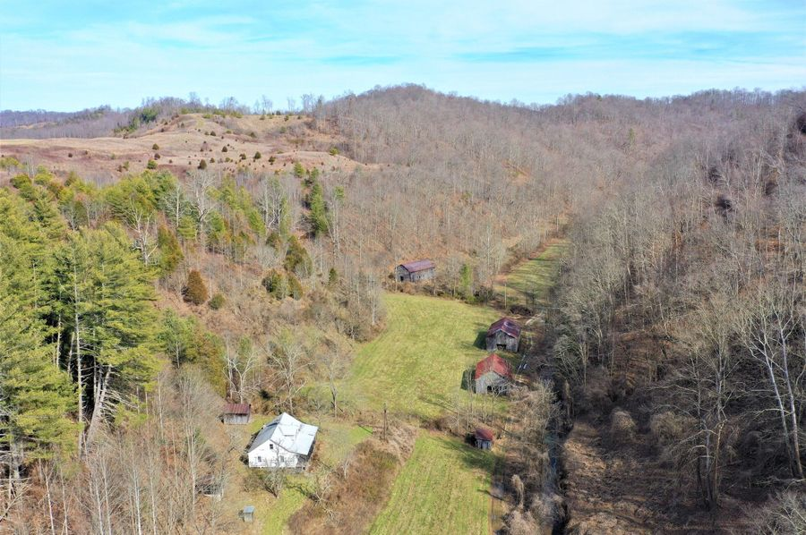 001 drone shot near the northwest entry to the property showing 1 of the 2 farmhouses located on the property
