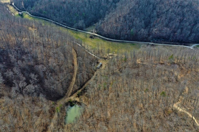 004 gorgeous aerial drone shot of the pond, creek, fields, and main pavement road