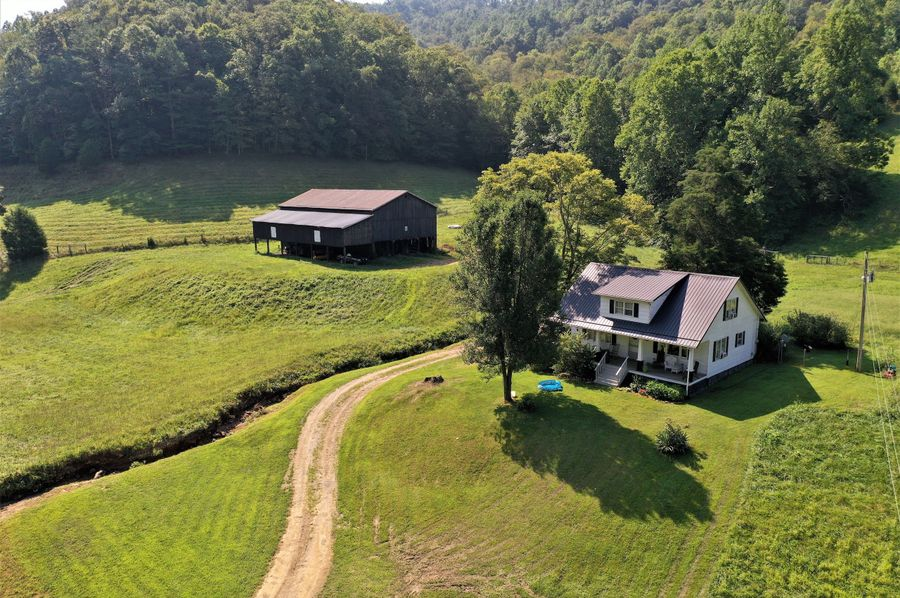 001 low elevation drone shot of the home and barn